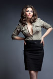 Military. Girl in military khaki shirt and narrow black skirt. studio portrait Royalty Free Stock Images