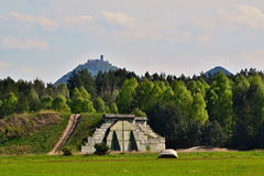 Military aircraft concrete shelter with castle on hill top in background Royalty Free Stock Photos