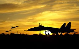 Airfield. Military aircrafts silhouettes  on sunset background Stock Photos
