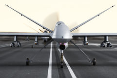 Military armed UAV drones preparing for takeoff on a runway. Royalty Free Stock Images