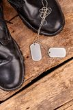 Military army boots and dog tags. Wooden background royalty free stock images