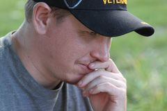 Military Army Veteran thinking with hand to face. Young Generation X Operation Iraqi Freedom Veteran with hand to face slightly smiling Stock Photos
