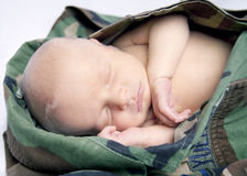 Military Baby. Infant in military BDU top. Baby is sleeping peacefully snuggled up in the US Military fatigues stock image