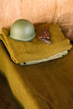 Military bed with helmet and pistol Stock Photo