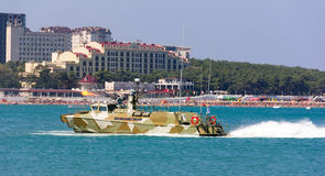 Military boat blank volley of guns on the city beach Stock Image