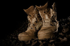 Military boots on camouflage net Stock Photos