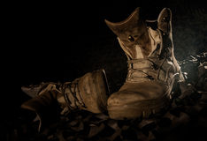 Military boots on camouflage net Royalty Free Stock Images