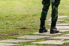 Military Boots of Soldier in camouflage Pants on Grass. Military Boots of Soldier in camouflage Pants on Green Grass stock image