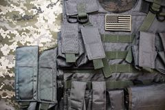 Military bulletproof vest with american flag badge. Upper view photo of tactical military bulletproof vest with american flag badge laying on camouflage cloth royalty free stock photos