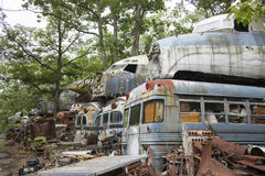 Military buses and aircraft in junkyard. Cockpit units of wrecked military aircraft on top of transport busses in junkyard Royalty Free Stock Image