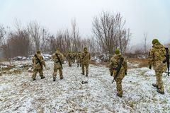 The military in camouflage with Kalashnikov assault rifles, behind their backs, go forward to attack the enemy in winter.  royalty free stock photo