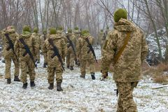 The military in camouflage with Kalashnikov assault rifles, behind their backs, go forward to attack the enemy in winter.  stock photos