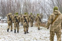 The military in camouflage with Kalashnikov assault rifles, behind their backs, go forward to attack the enemy in winter.  royalty free stock image