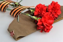 Military cap, carnations tied with Saint George ri Royalty Free Stock Photography
