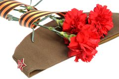 Military cap, carnations tied with Saint George ribbon isolated Royalty Free Stock Photography