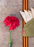 Military cap and red flowers with orange ribbon lie on old paper. Military cap and red flowers with orange ribbon lie Royalty Free Stock Photography