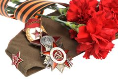Military cap, red flowers, Saint George ribbon, or Royalty Free Stock Image