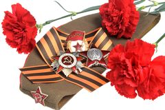 Military cap with red flowers, Saint George ribbon, orders of Great Patriotic war Royalty Free Stock Image
