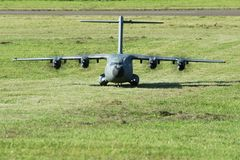 Military cargo airplane(A-400M)-landing on grass runway. Military cargo airplane doing some special training landings and takeoffs  on a gras strip Stock Image