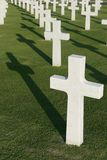 Military Cemetery. White marble crosses in a military cemetery casting their shadows on the grass Royalty Free Stock Photos