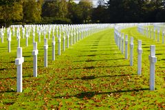 Military Cemetery Crosses. Blue sky and sunshine at the American military cemetery Henri-Chapelle near Aubel in Belgium, some foliage in the foreground Royalty Free Stock Photo
