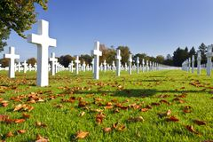 Military Cemetery Crosses. Blue sky and sunshine at the American military cemetery Henri-Chapelle near Aubel in Belgium, some foliage in the foreground Stock Photo