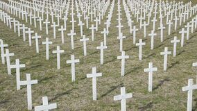 Military cemetery with white crosses. Headstones in War memorial. Numerous soldier`s graves marked with Christian crosses. The fa