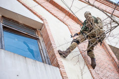 Military climber storm window of the building. Armed soldiers on a rope with a firearm aims at the window of the building that is going to storm stock photo