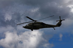 Military combat helicopter. Against cloudy sky Stock Photos