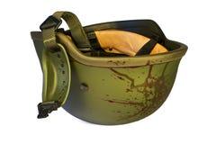 Military combat helmet inverted, blood splattered Stock Photography