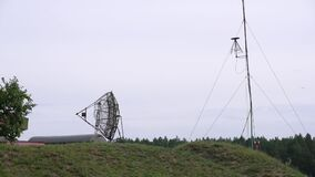 Military combat radar in army paint with clear cloudy sky. Radar disguised in green forest transmitting radio waves to