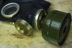 A black gas mask with a membrane for talking lies on wooden boards. A military concept is a chemical or radioactive attack or an e. A military concept is a Stock Images