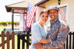 Military couple hugging. American military couple hugging outside home royalty free stock images