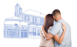 Military Couple Looking At House Drawing on White. Embracing Military Couple Looking At House Drawing on White royalty free stock photography