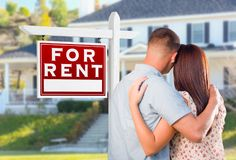 Military Couple Looking At House with For Rent Real Estate Sign stock images