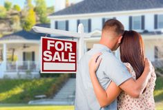 Military Couple Looking At House with For Sale Real Estate Sign stock images