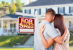 Military Couple Looking At House with Sold For Sale Realty Sign Royalty Free Stock Image