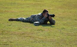 Military Crouching on Green Grass Using Dslr Camera during Daytime stock photo
