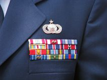 Military decorations on uniform. Close-up of a blue military dress uniform jacket displaying a medal above various awards, decorations and ribbons Stock Photos