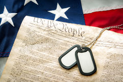 Military dog tags, the US Constitution and the American flag Stock Photo