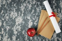 Military education concept. Books, scroll paper, pencils. And apple on camouflage background royalty free stock image