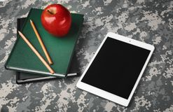 Military education concept. Tablet, books, pencils and apple. On camouflage background stock image