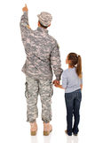Military father daughter pointing. Back view of military father and his daughter pointing at empty space stock image