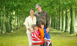 Military father and his family standing with american flag. In park stock image