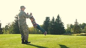 Military father playing and spinning with his daughter in the park. Soldier vacation, having fun with adorable daughter in the park lawn stock footage
