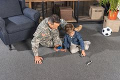Military father and son playing with toys while sitting on floor. At home stock images