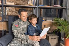 Military father and son using tablet together while sitting. In armchair stock image