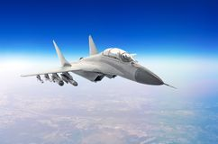 Military fighter aircraft at high speed, flying high in the sky. Stock Photos