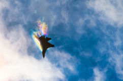 A military fighter high in the sky, piercing clouds of vapor breaks, rainbow light. Royalty Free Stock Photos