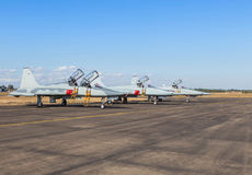 Military fighter jet aircrafts parked on runway in airforce base. Row of military fighter jet aircrafts parked on runway in airforce base on blue sky background royalty free stock photography